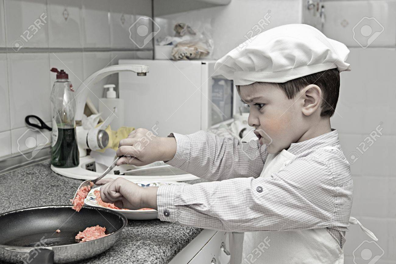 Child Dressed As A Chef Working In The Kitchen Stock Photo, Picture ...