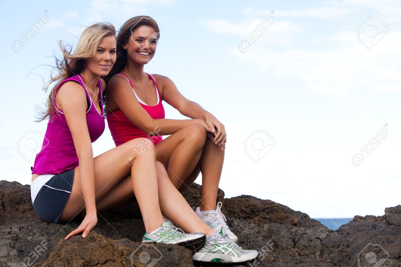 1f93f0c2f0 Low angle portrait of two young women sitting on rocks at the beach. They  are