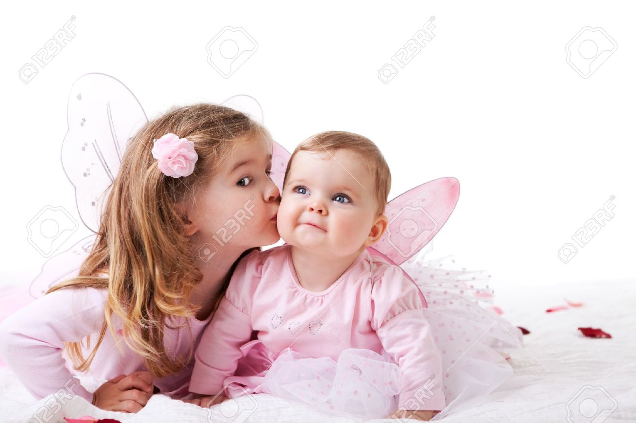 Two sisters are dressed up as fairies.  The older sister is kisssing the baby sister on the cheek.  Horizontal shot. Stock Photo - 7157255