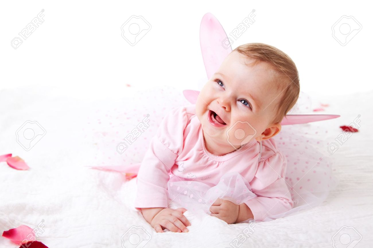 A Cute Baby Girl In Fairy Wings Laughs While Lying On The Ground Stock Photo Picture And Royalty Free Image Image 7157239