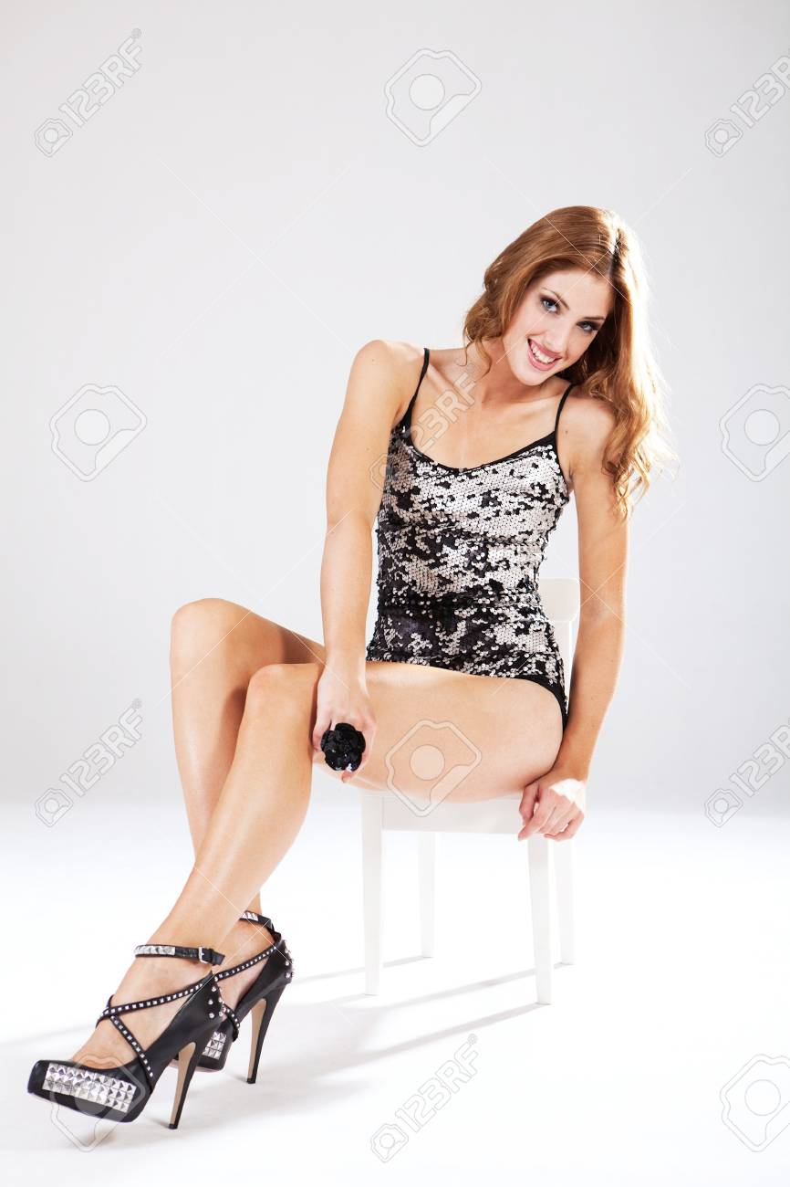 Beautiful young woman in one-piece lingerie sits in a white chair while smiling into the camera. Vertical shot. Stock Photo - 7501320
