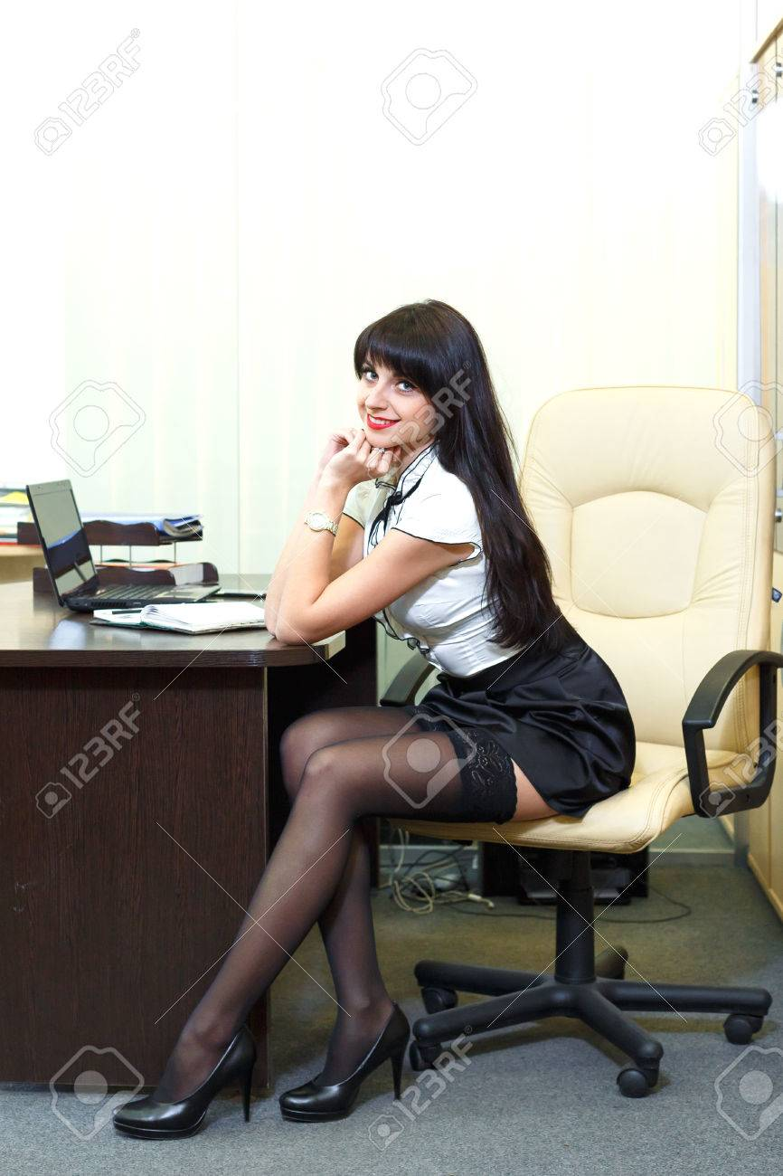 e7e06449711 Stock Photo - Young sexy woman in black stockings sitting on workplace in  the office