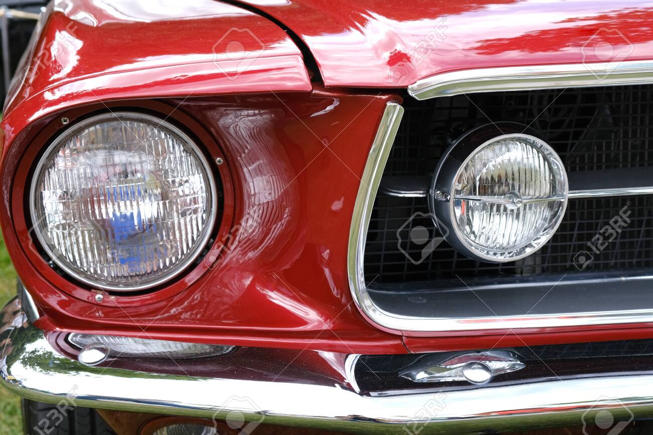 Headlights , radiator and hood of old retro red car ckose-up. - 130716557