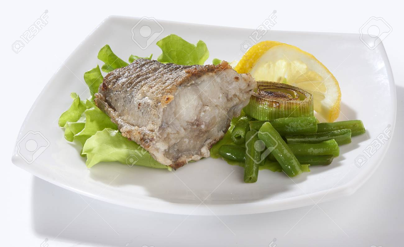 Fried piece of cod with lettuce, lemon, string beans and leek on the plate Stock Photo - 14060554