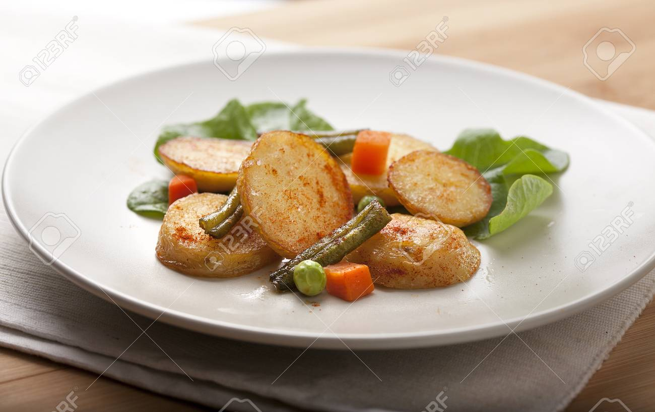 Fried potato with lettuce and vegetables on the white plate Stock Photo - 18381899
