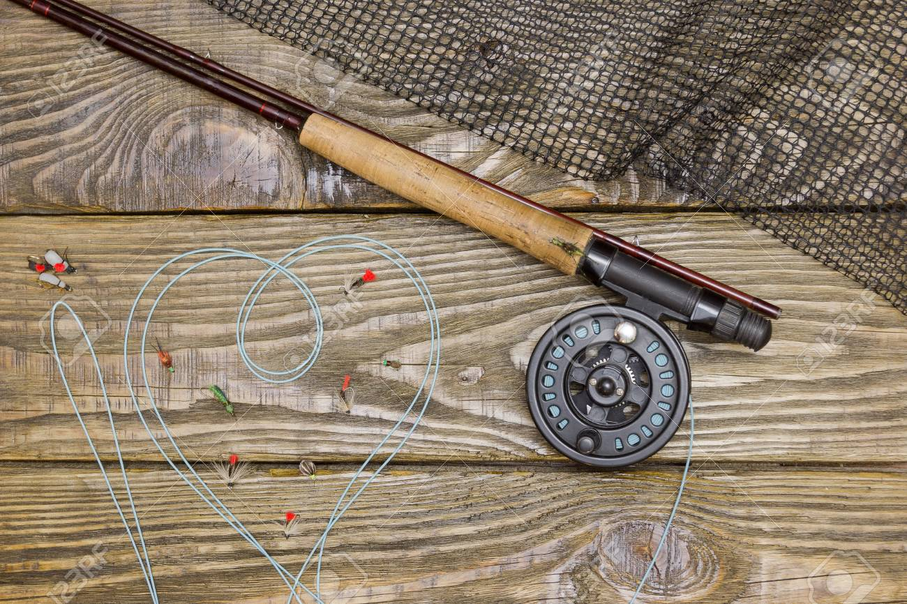Fly Fishing Rod Flie And A Landing On The Old Wooden Table