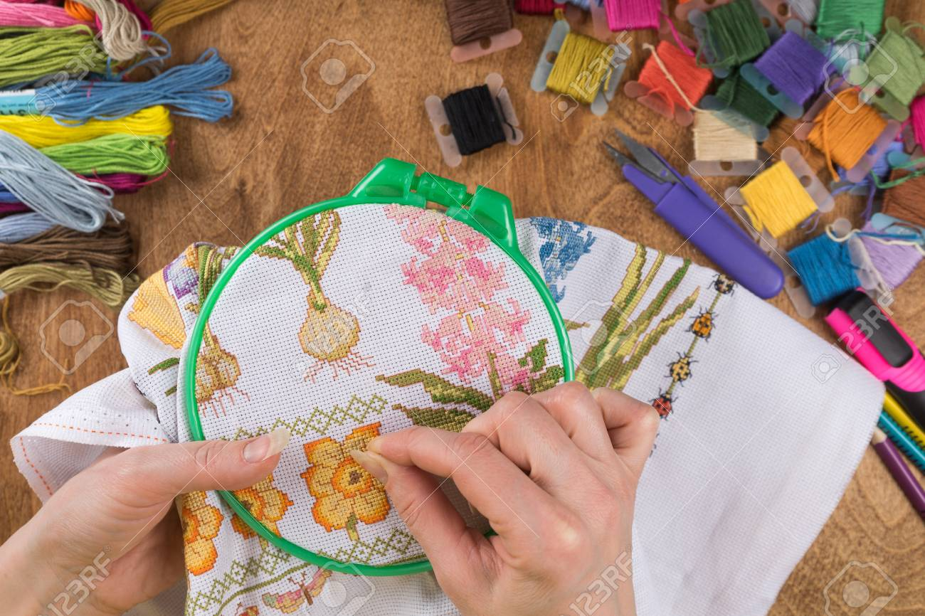 Girl sitting at a table where everything is necessary for embroidery, embroiders a big picture. Copy paste. - 94831326