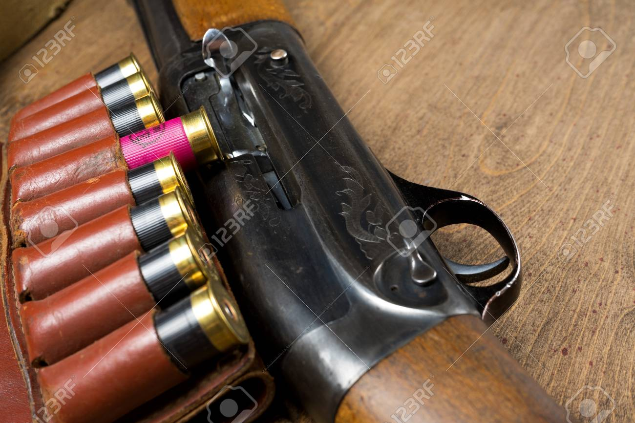 Hunting rifle and ammunition lie on a wooden background - 97505217