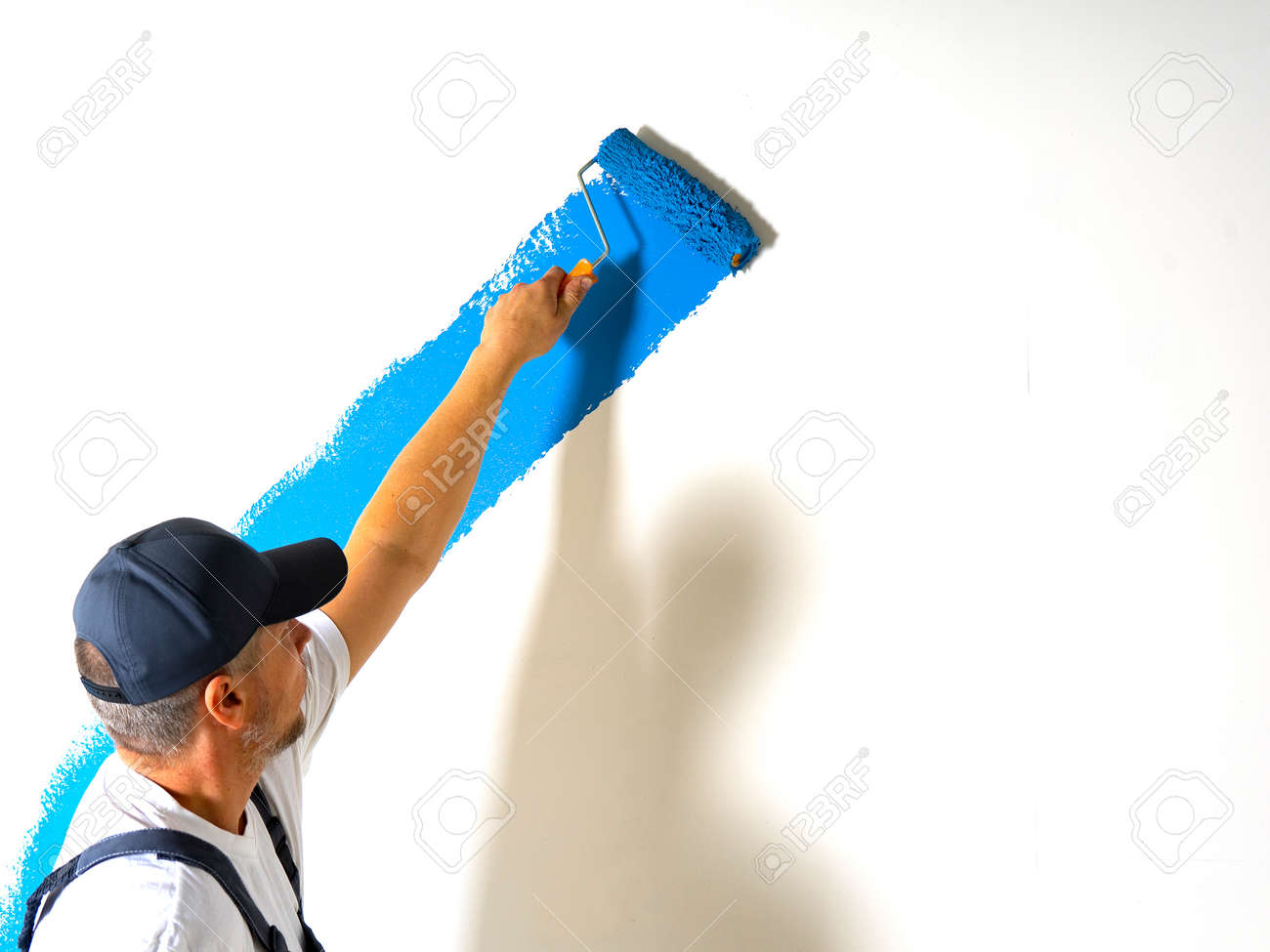 Male painter painting a white wall with a roller in blue color renovations or construction concept - 170234520