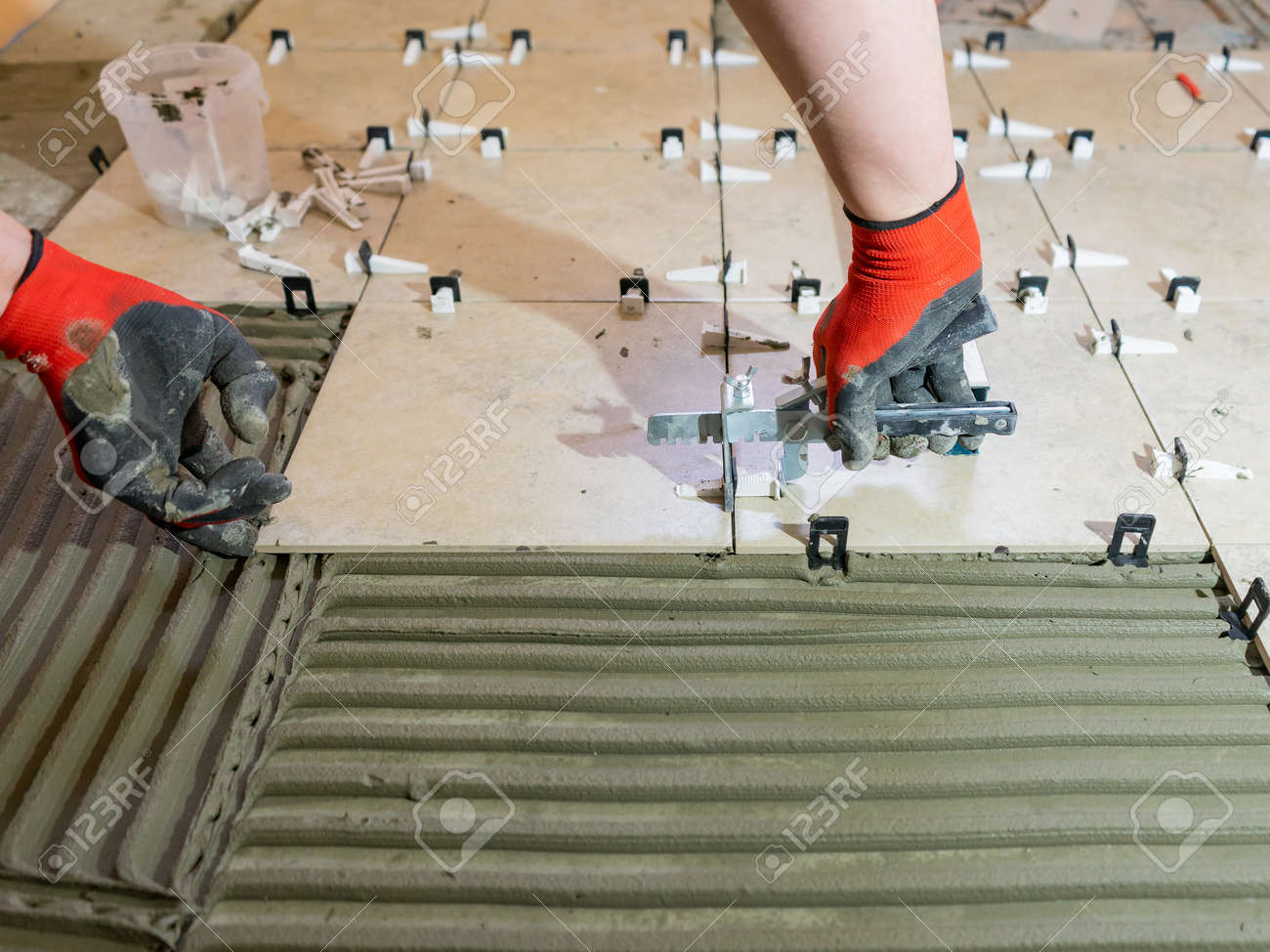A worker is leveling the ceramic tile with wedges and clips. Tile leveling system - 171010421