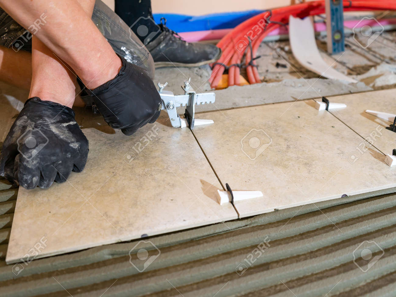 Workers are using plastic clamps and wedges to leveling the ceramic tile on the floor. Tile leveling system. - 171996055