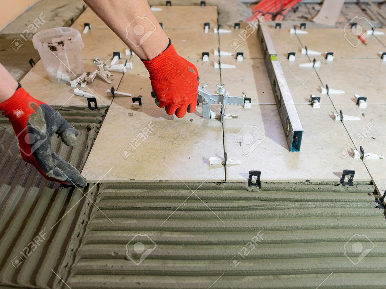 A worker is leveling the ceramic tile with wedges and clips. Tile leveling system - 171995161