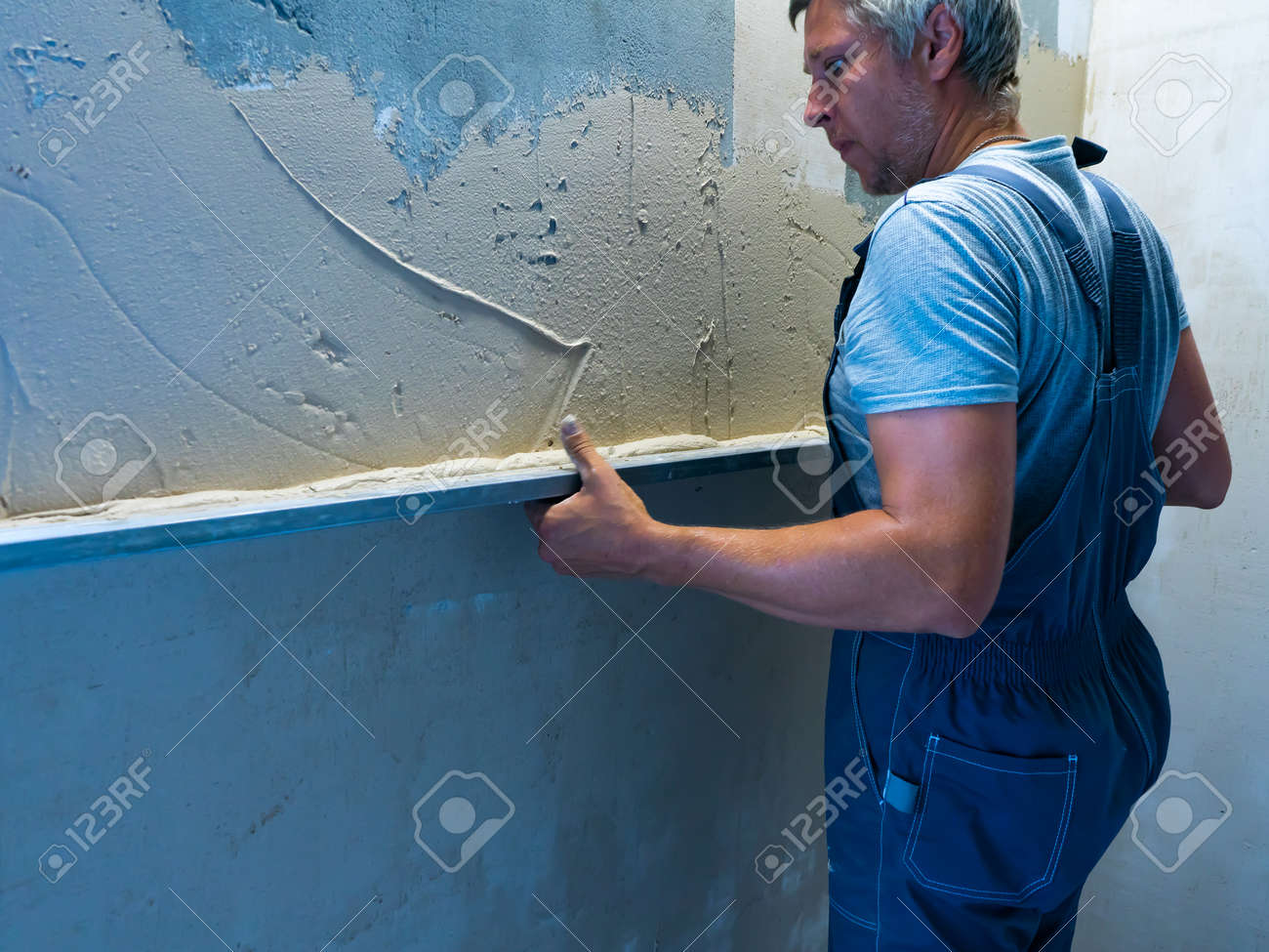 Applying plaster putty to the wall using a aluminum paver screed. - 172149536