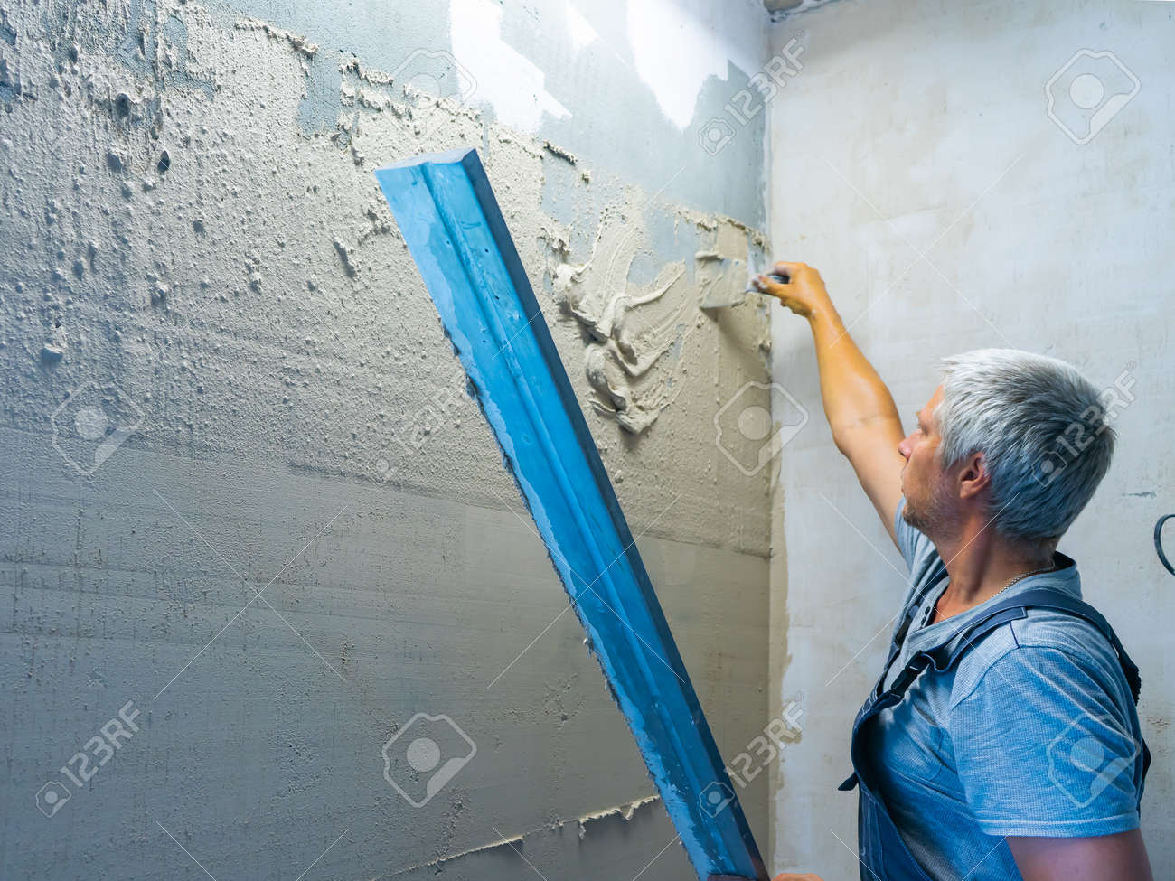 Applying plaster putty to the wall using a aluminum paver screed. - 172149539