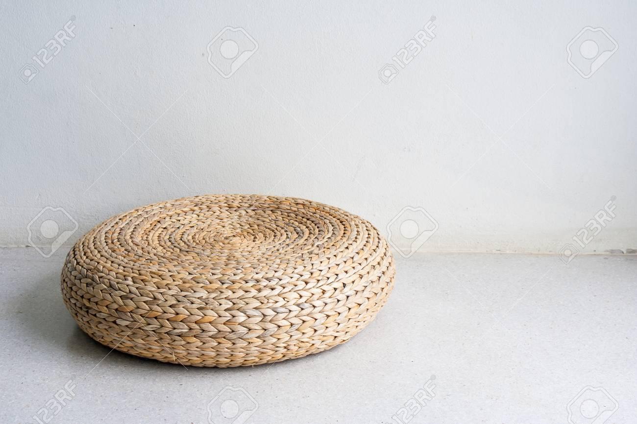 Chaise ronde en osier brun dans un décor de style vintage sur un sol en  béton dans une salle blanche éclairée par la lumière naturelle.