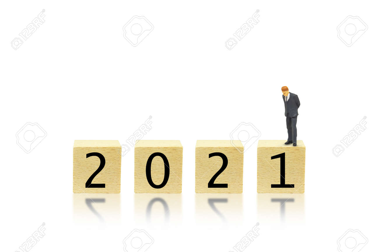 Business and 2021 New Year Concept : Miniature as businessman bend down to look at 2021 wording text on wooden blocks. - 155261239