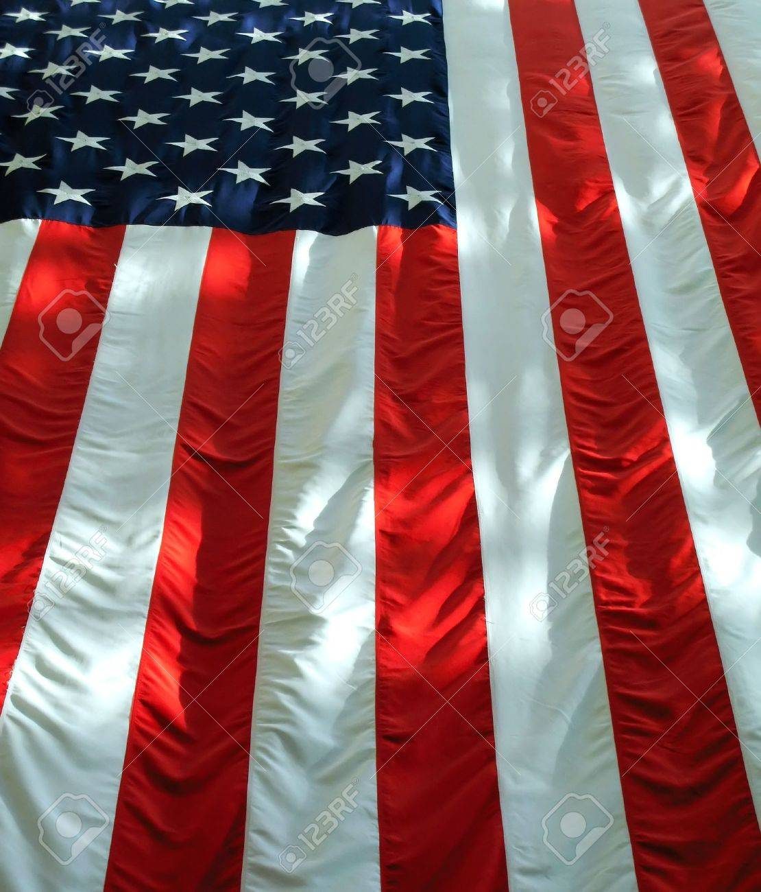 Vertically hung American flag with light and shadows. Stock Photo - 3293873