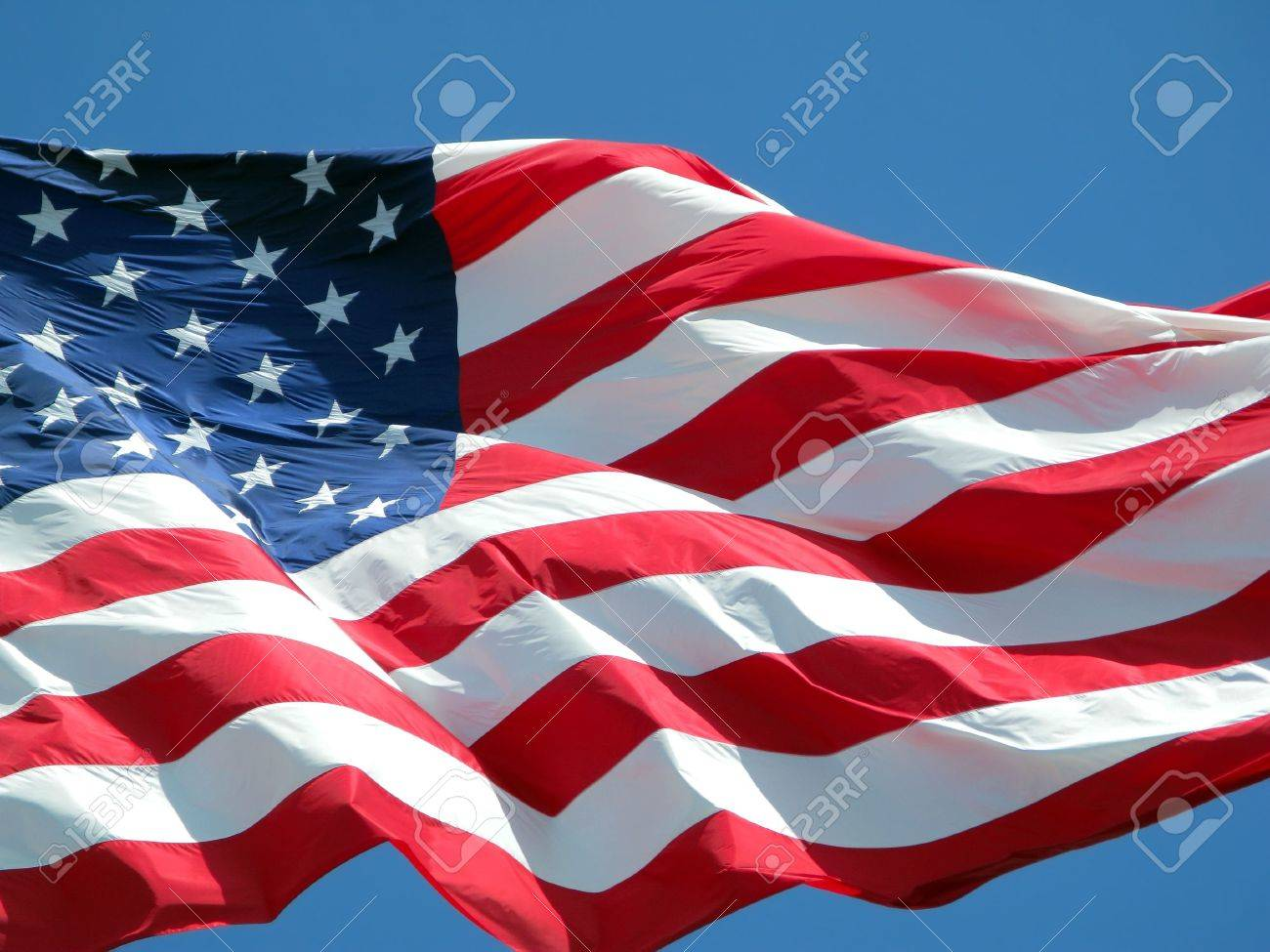 Waving American flag against a blue sky background. Stock Photo - 3294139