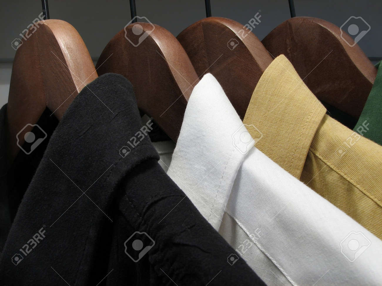 Black, white, yellow and green shirts on wooden hangers. Stock Photo - 719775