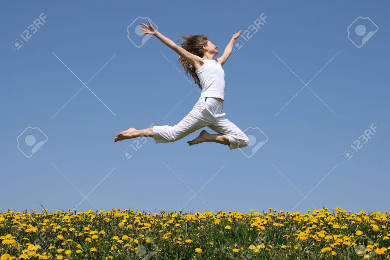 Girl in summer white clothes flying in a jump over flowering dandelion field. Stock Photo - 963880