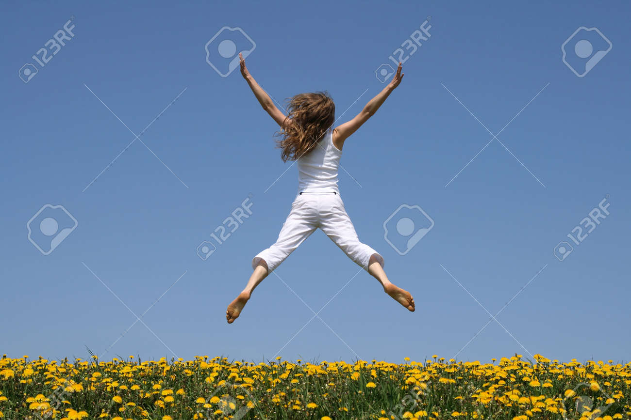 Girl in summer white clothes flying in a funny jump over flowering dandelion field. Stock Photo - 963881
