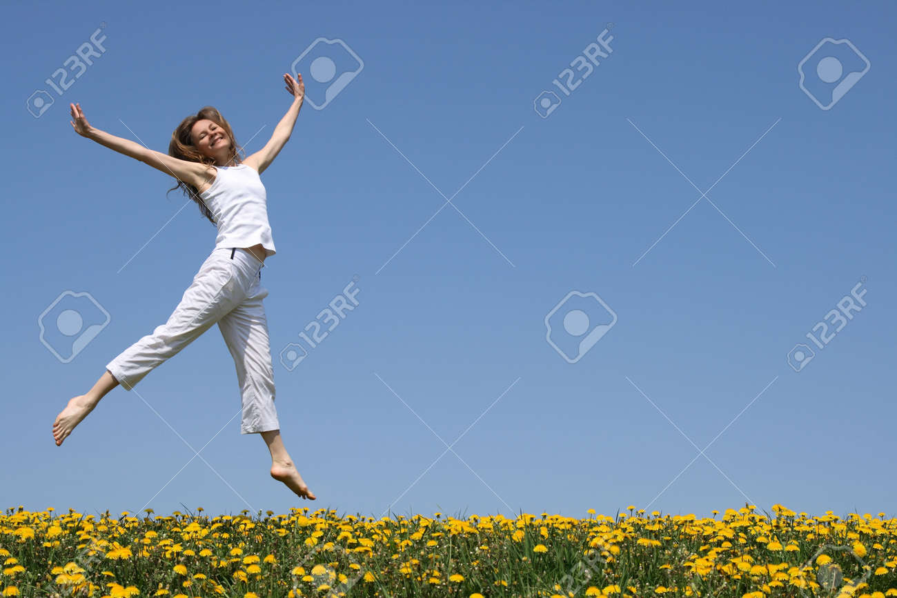 Smiling pretty girl in summer white clothes dancing in a flowering meadow. Stock Photo - 968013
