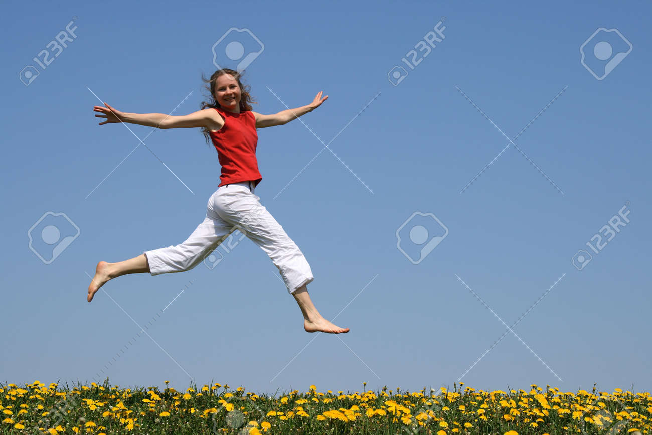 Girl in red t-shirt flying in a jump over flowering dandelion field. Stock Photo - 998873