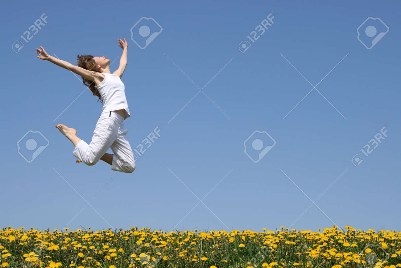 Young woman in a beautiful happy jump in flowering field. Stock Photo - 1010968