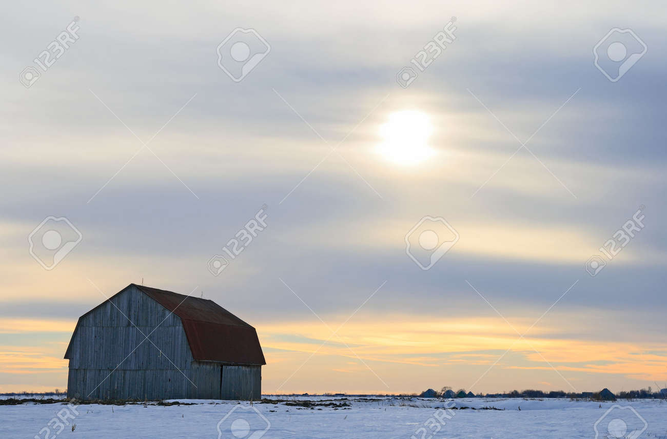 Old wooden barn in a snowy field in the evening. Stock Photo - 2571408