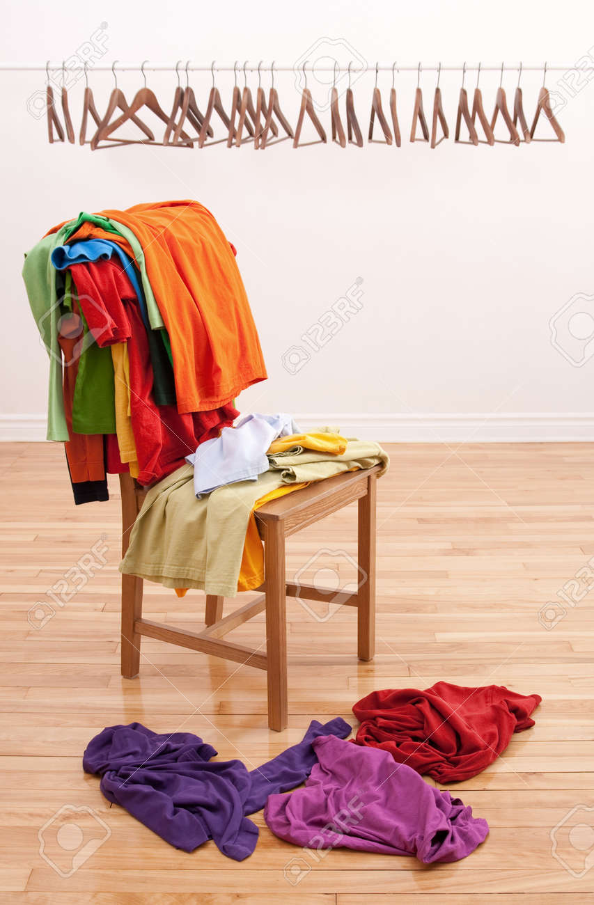 Colorful messy clothes on a chair and row of empty hangers on the background. Stock Photo - 8796293