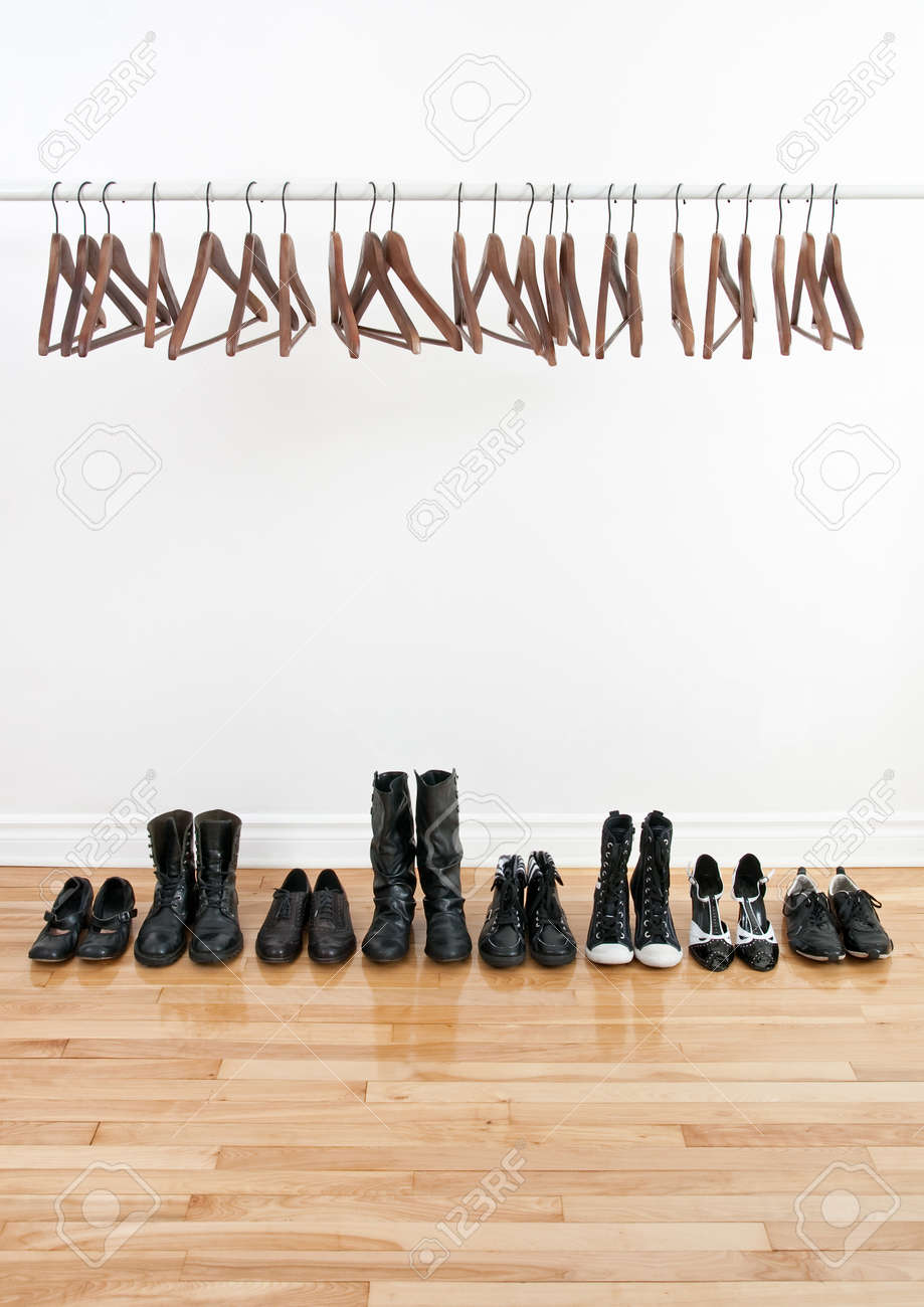 Row of black shoes and boots on a wooden floor, and empty hangers on a rod. Stock Photo - 9071198