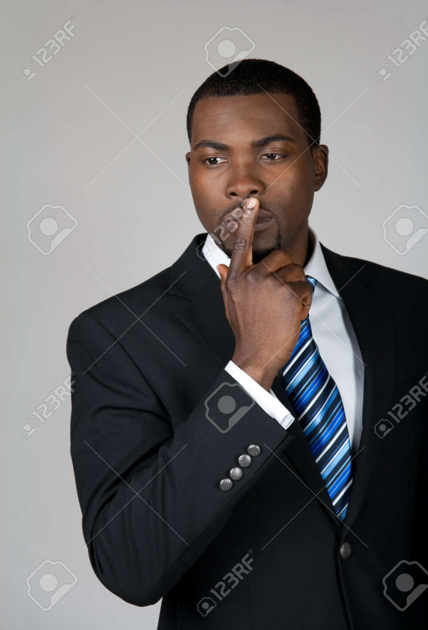 African American business man thinking and holding a finger on his lips. Stock Photo - 9455307