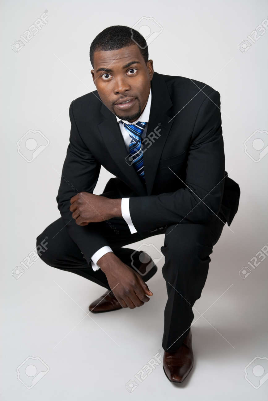 African American business in black suit squatting. Stock Photo - 9455308