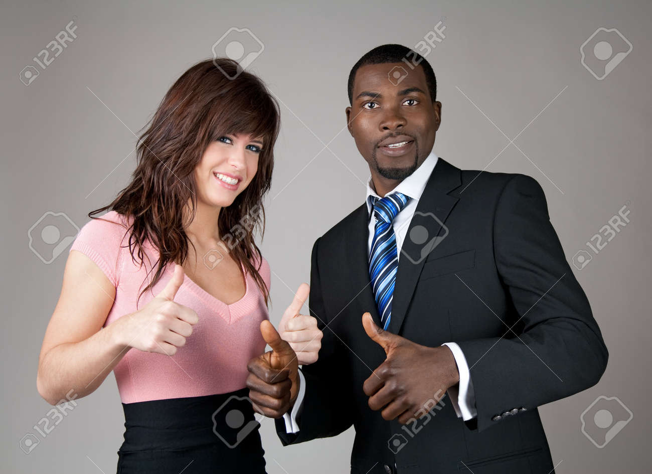 Male and female business partners going thumbs up. Stock Photo - 9455343