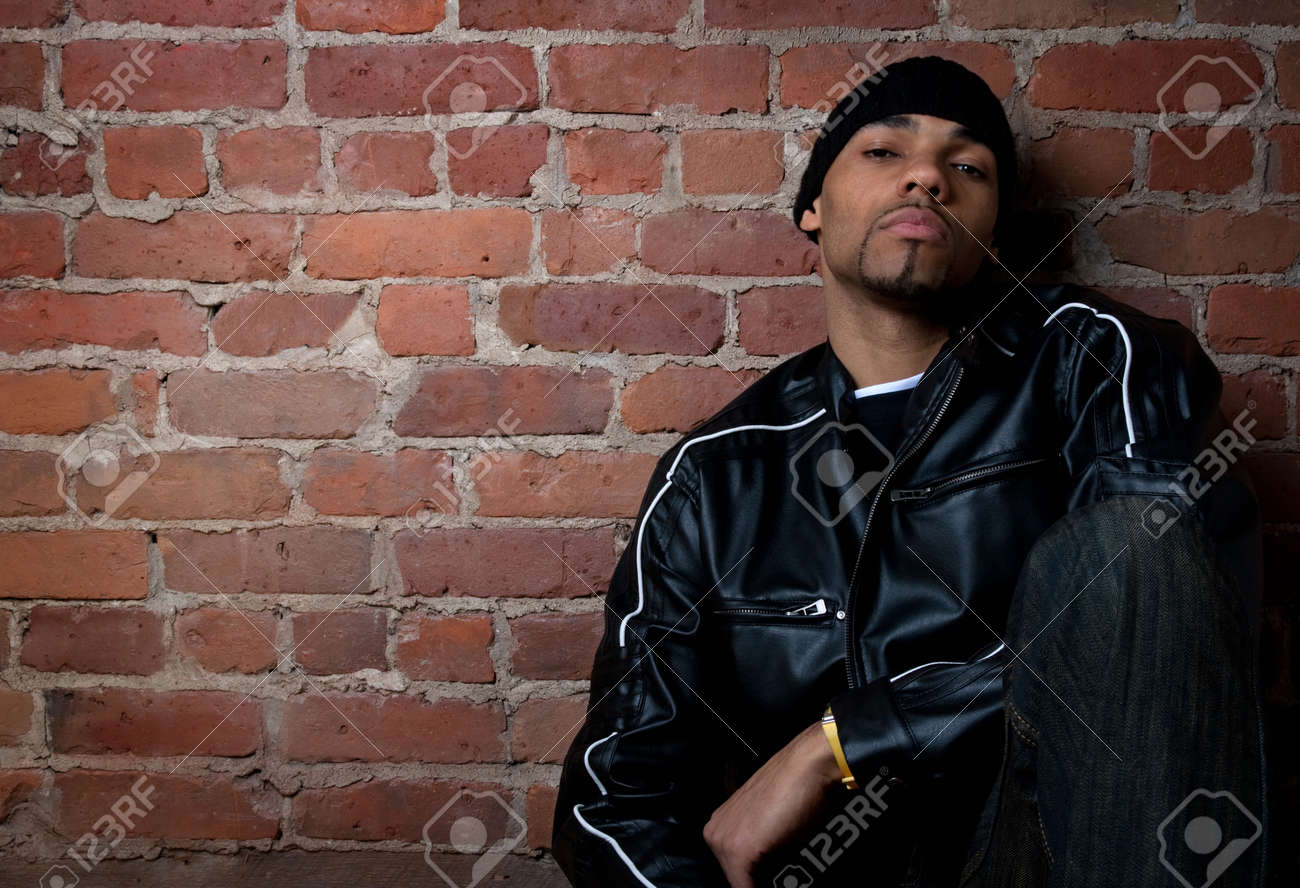 Gloomy street guy dressed in black, sitting near a brick wall. Stock Photo - 9710789
