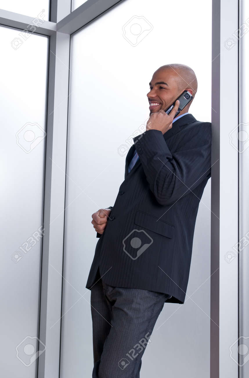 Businessman leaning against the window, talking on the phone and smiling. Stock Photo - 10763848