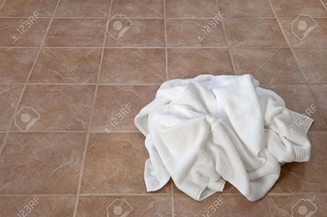 Bathroom floor towels - Creased White Towels On Ceramic Floor In A Laundry Room Or Bathroom Stock Photo