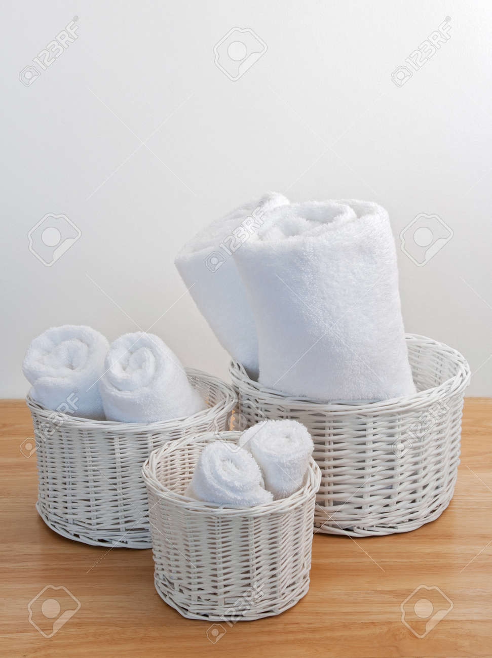 clean towels in white wicker baskets on a wooden surface stock photo