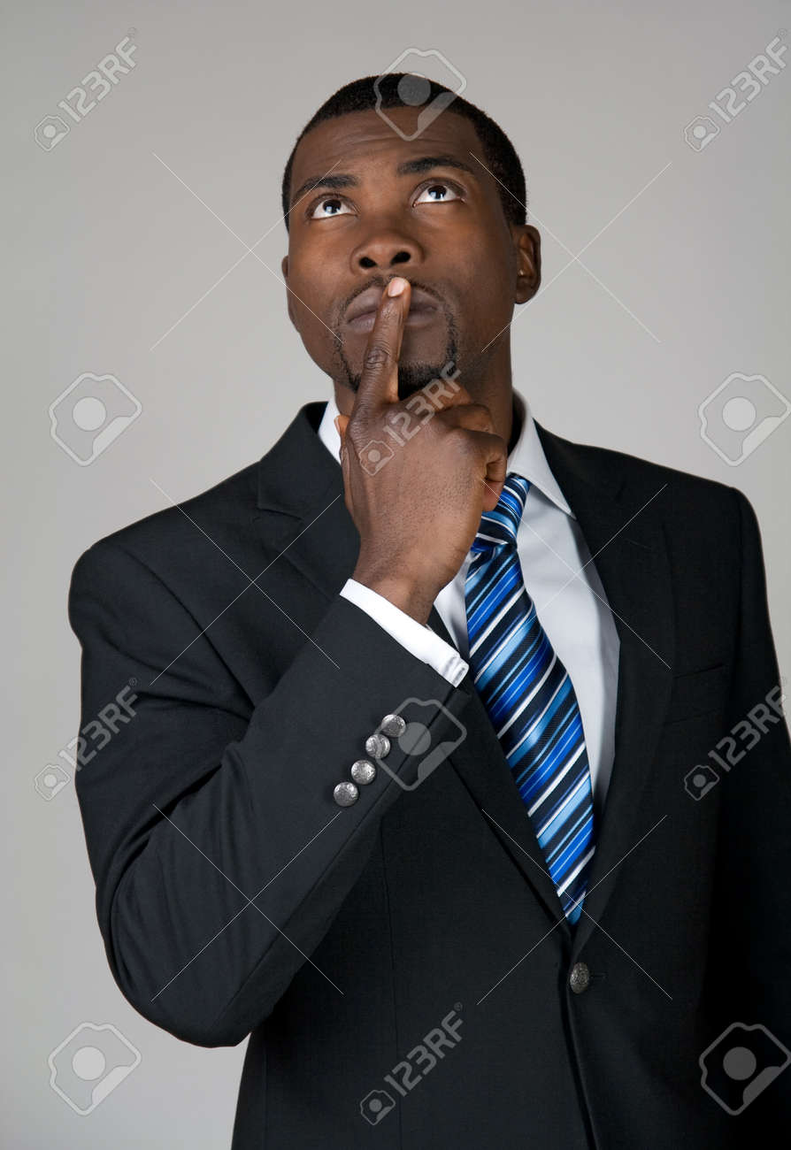African American businessman looking up and thinking, holding a finger on his lips Stock Photo - 12972866