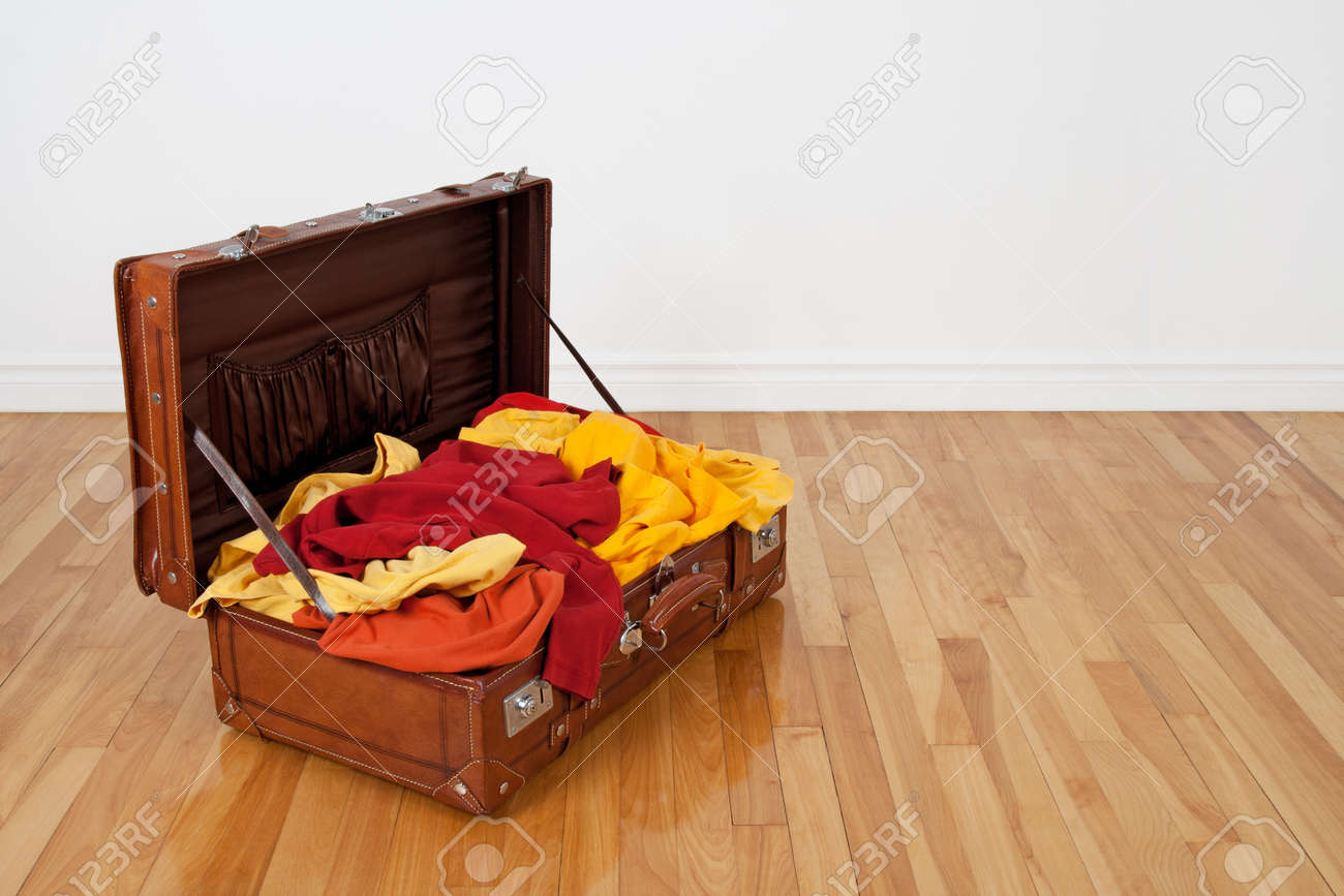 Leather suitcase on the wooden floor, full of orange, red and yellow clothing Stock Photo - 13297757