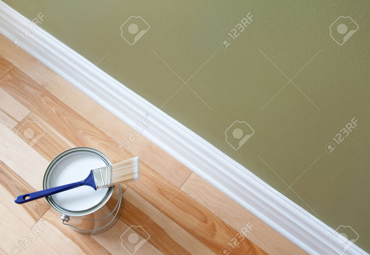 Newly opened can of white paint and paintbrush on wooden floor Stock Photo - 15013134