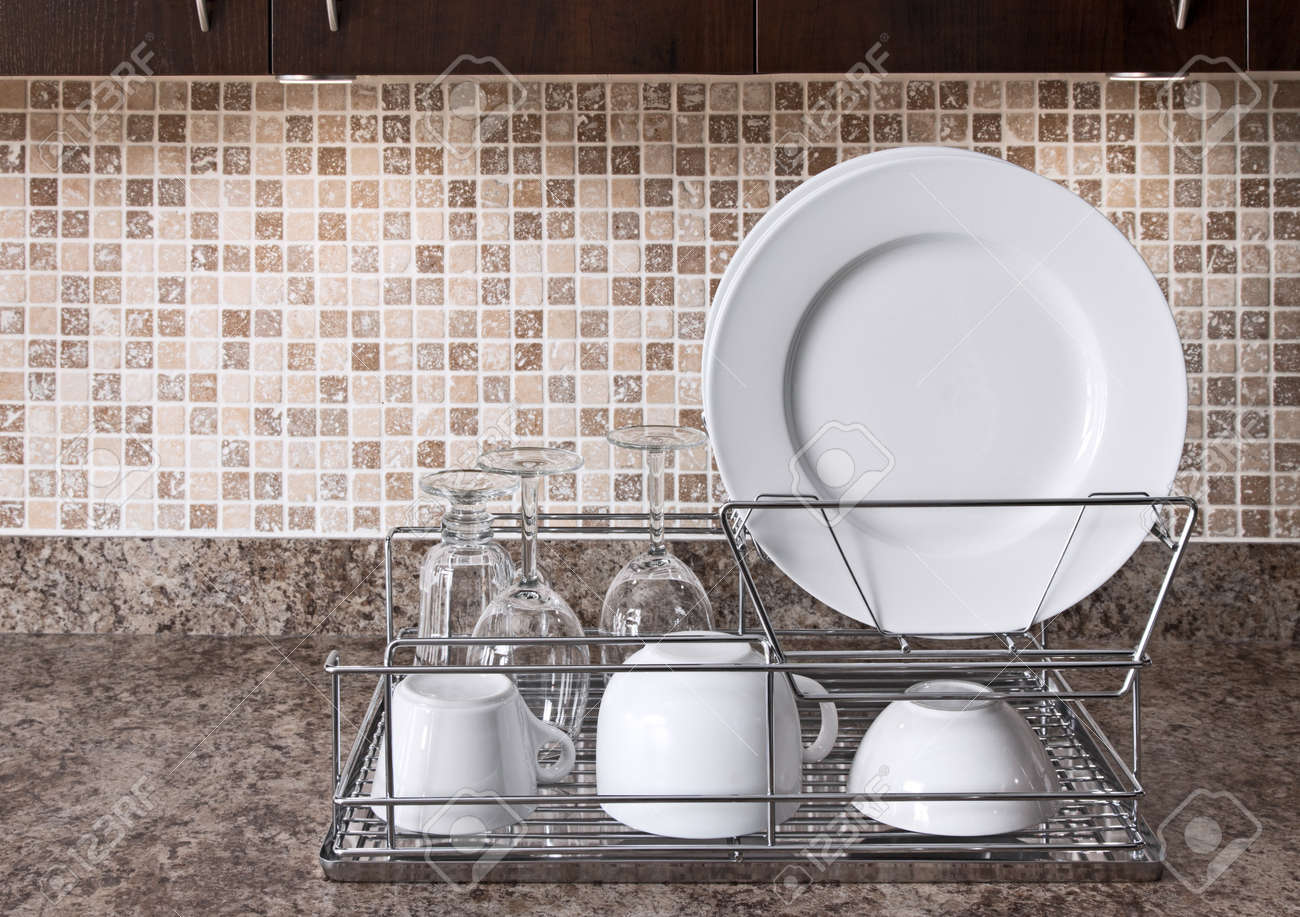 Afdruiprek met witte borden en kopjes op aanrecht in de keuken ...
