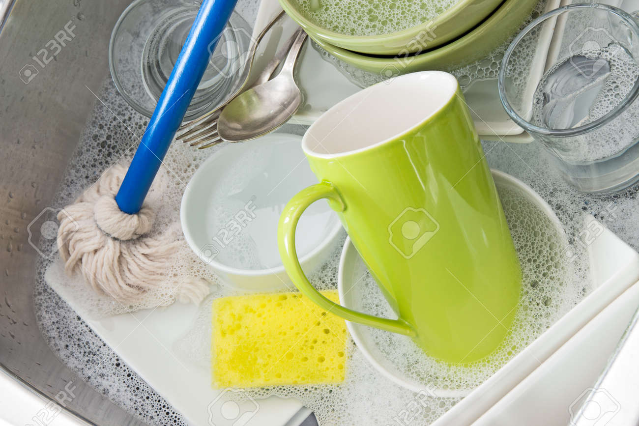 Washing bright dishes in the kitchen sink Stock Photo - 16729056