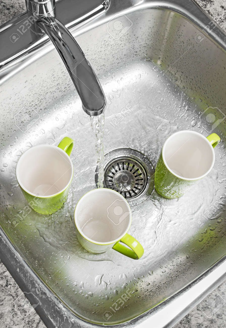 Washing green cups in the kitchen sink  Water running from the tap Stock Photo - 16729057