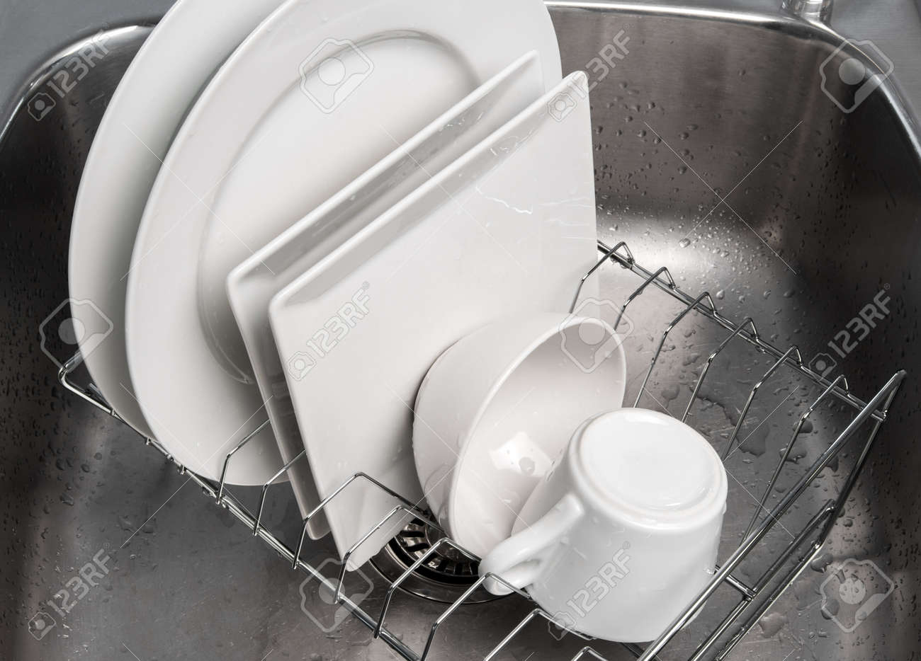 White clean dishes drying on a rack in the kitchen sink Stock Photo - 16729050