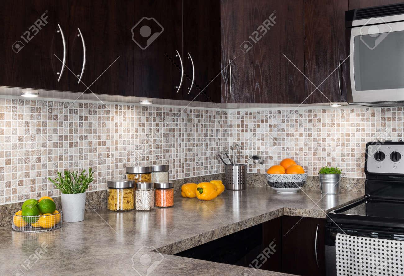 Modernt kök med mysig belysning och livsmedelsingredienser på bänk ...