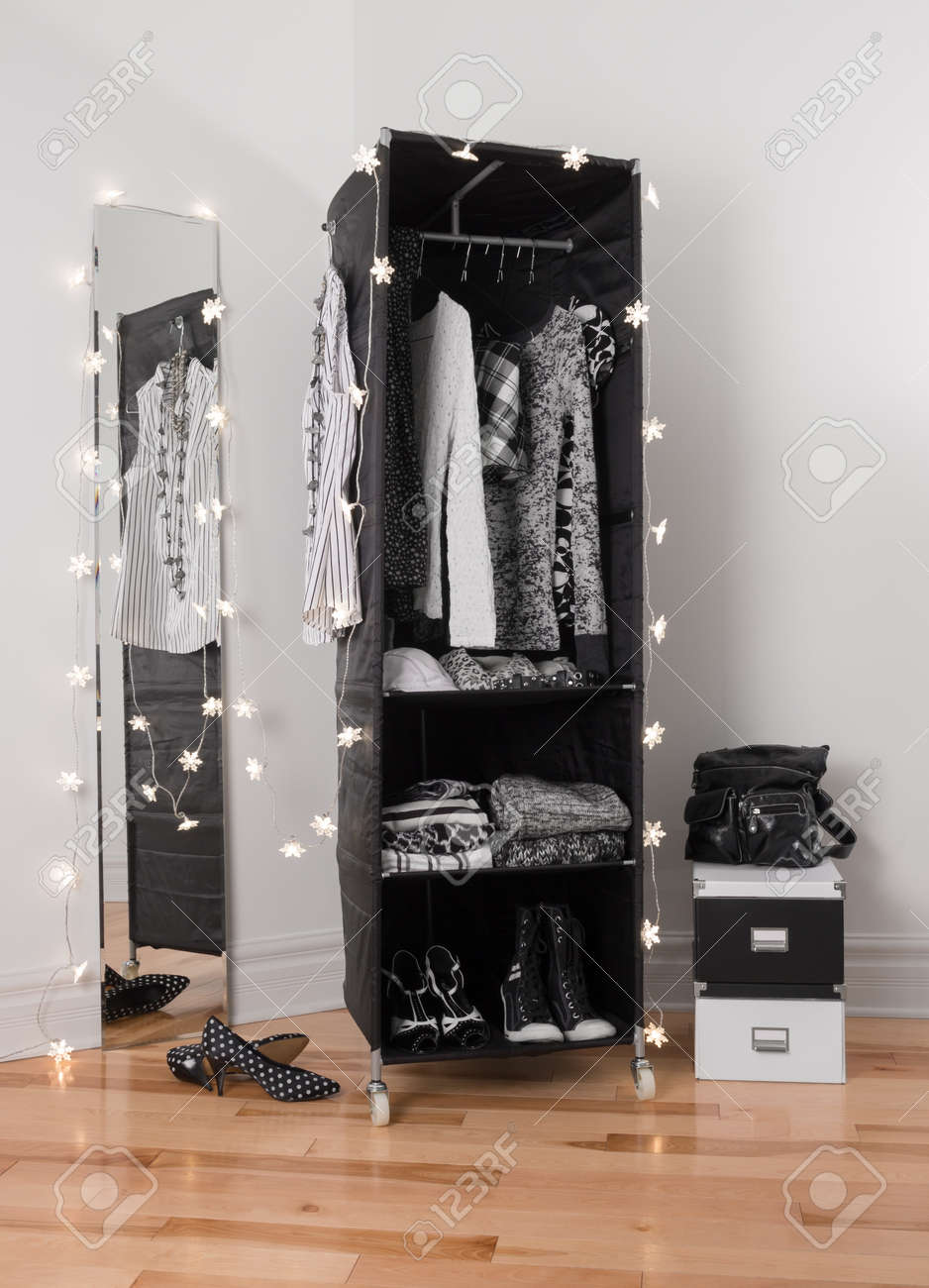 Lights Decorating A Mirror And Clothes Organizer With Black White Clothing Stock Photo