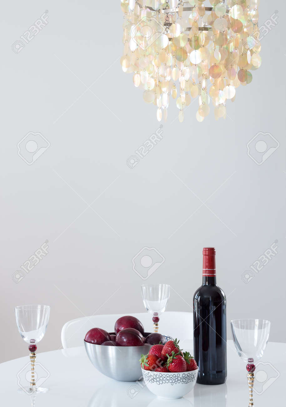 Red wine and fruits on a table, in a room decorated with beautiful chandelier Stock Photo - 20178960