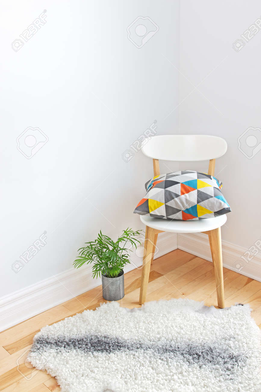 Home Decor Chair With Bright Cushion Plant And Sheepskin Rug On The Floor Stock Photo
