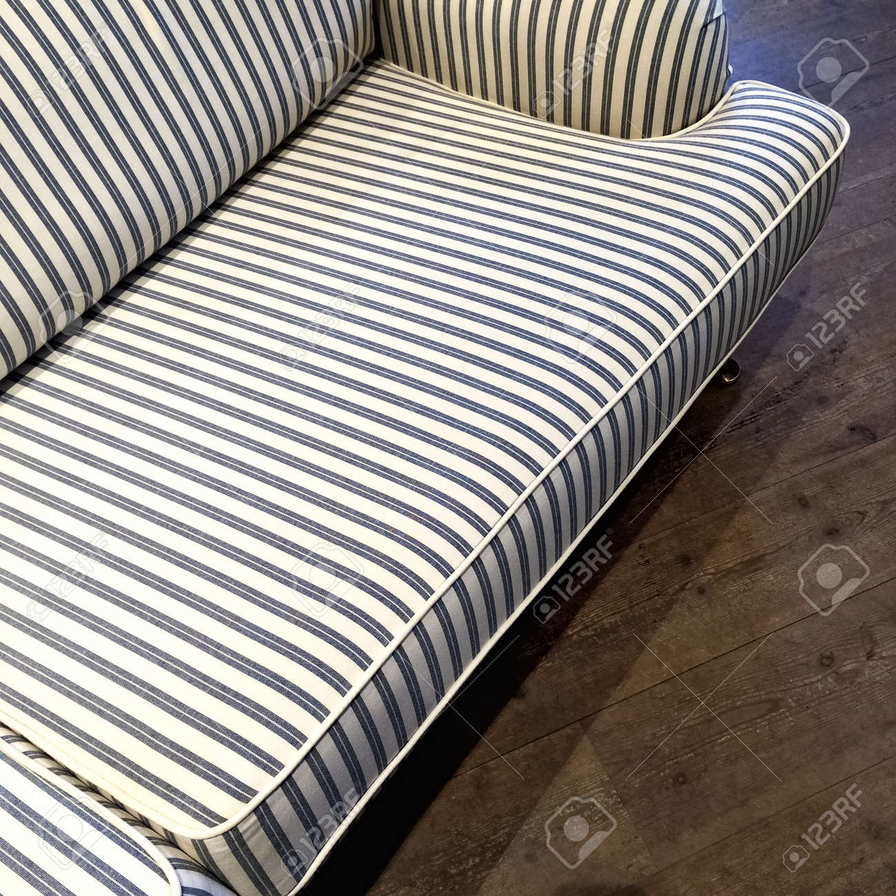 Elegant blue and white striped sofa on dark wooden floor.